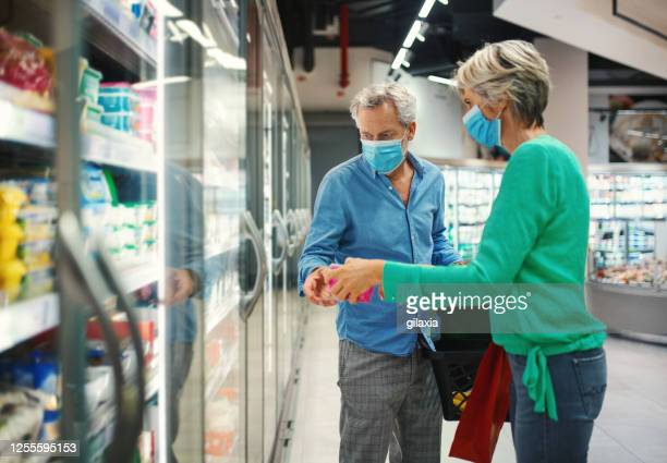 mid aged couple in a supermarket during coronavirus. - frozen food stock pictures, royalty-free photos & images