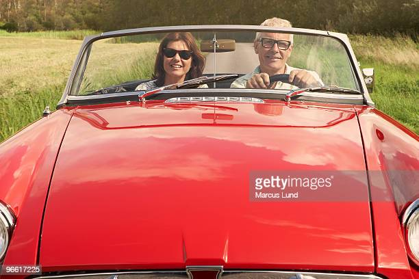 Mid aged couple in sports car