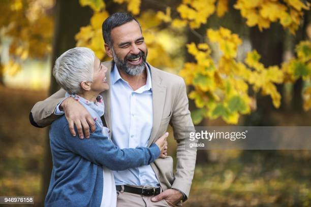 Mid aged couple walking in a park.
