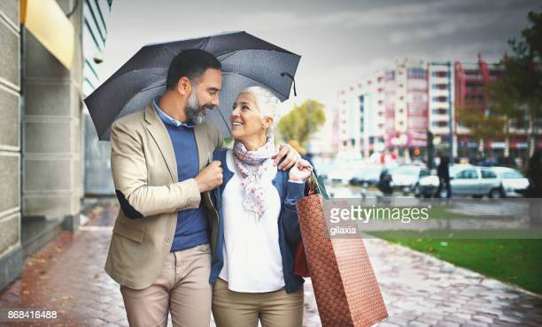Mid aged couple walking on a rainy day.