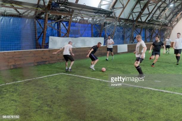 midden leeftijd mannen spelen amateur voetbal in schaatshal - middenvelder atleet stockfoto's en -beelden