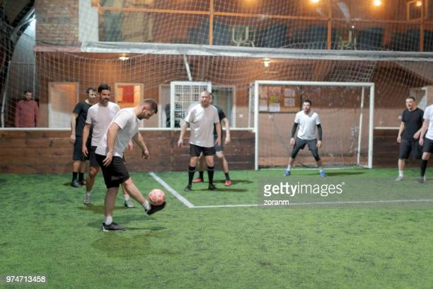 mid aged men playing amateur soccer indoors - amateur stock pictures, royalty-free photos & images