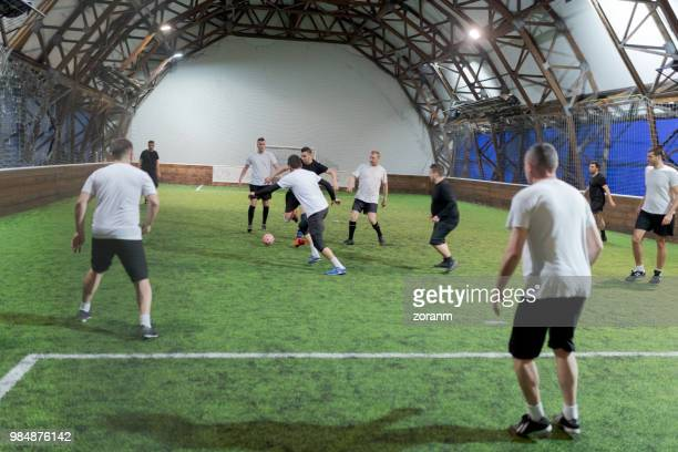 mid aged men playing amateur soccer indoors - soccer competition stock pictures, royalty-free photos & images