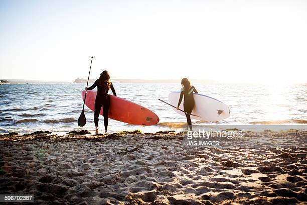 mid aged woman and teenage daughter paddle board - bournemouth england stock pictures, royalty-free photos & images