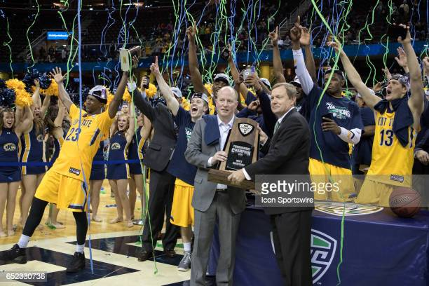 Mid American Conference commissioner Dr Jon Steinbrecher presents Kent State Golden Flashes head coach Rob Senderoff with the MAC Tournament trophy...