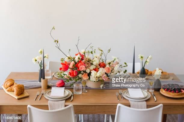mid century modern beautiful styled pink and wedding flowers on wooden table with place setting and invite - candlestick holder stock pictures, royalty-free photos & images