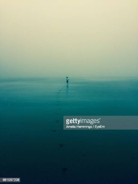 mid distance of boy running at beach against sky - mid distance stock pictures, royalty-free photos & images