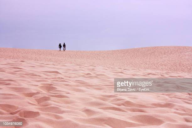 Mid Distance Of Friends Walking On Sand Against Clear Sky At Desert