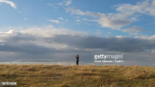 Mid Distance Of Man Standing On Grassy Field Against Cloudy Sky
