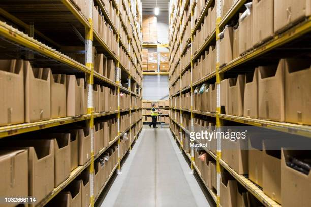 mid distance of mature female warehouse worker pushing cart seen through narrow aisle in industrial building - middlebare afstand stockfoto's en -beelden