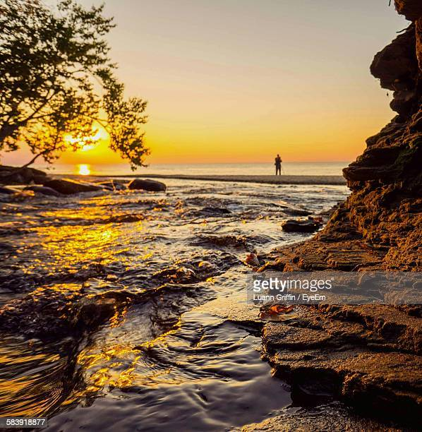 mid distance of person standing on beach during sunset - mid distance stock pictures, royalty-free photos & images