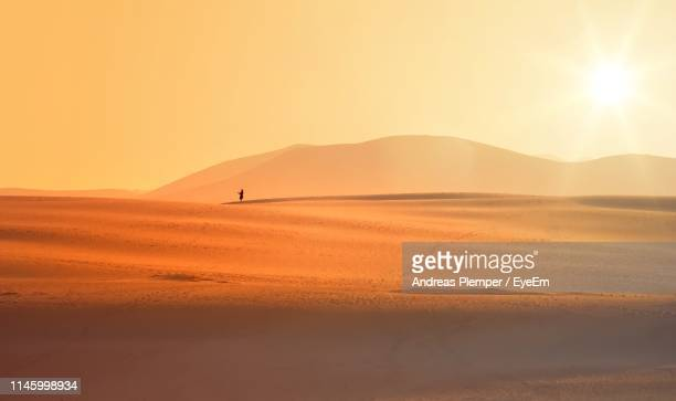 mid distance of person standing on desert against sky during sunset - andreas solar stock pictures, royalty-free photos & images