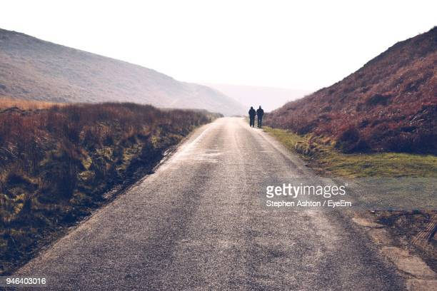 mid distance of silhouette friends walking on road amidst mountains - middlebare afstand stockfoto's en -beelden