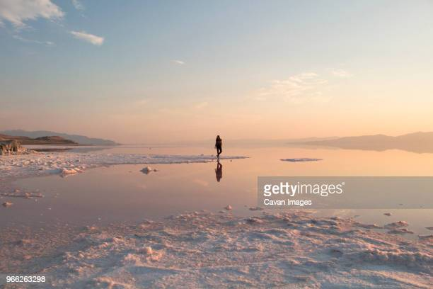 mid distance of woman standing at great salt lake during sunset - great salt lake stock pictures, royalty-free photos & images