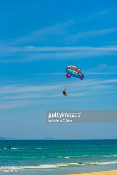 Mid distance shot of paragliding over sea and against sky