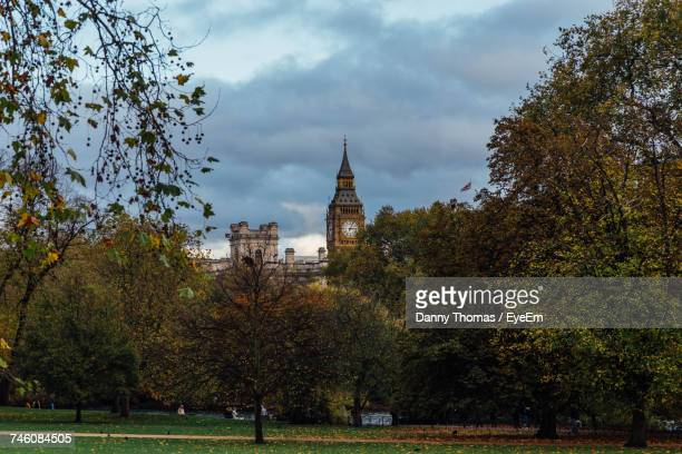 Mid Distance View Of Big Ben Seen From Park Against Cloudy Sky