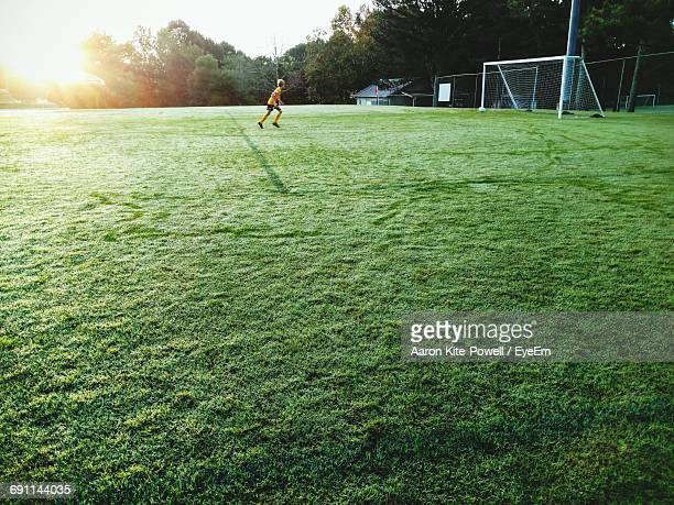 Mid Distance View Of Boy Playing Soccer On Field