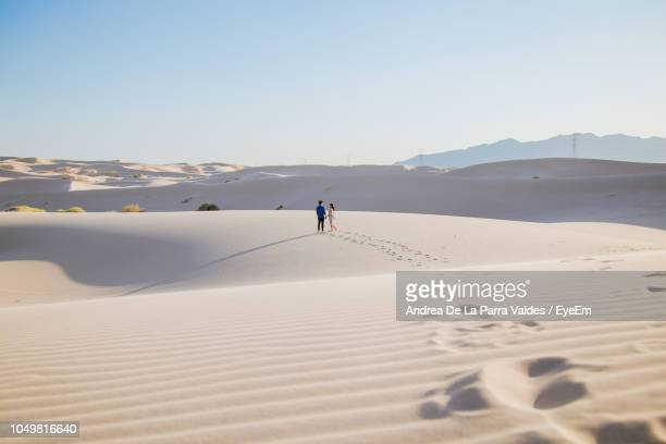 mid distance view of couple walking on sand at desert against sky - chihuahua desert stock pictures, royalty-free photos & images