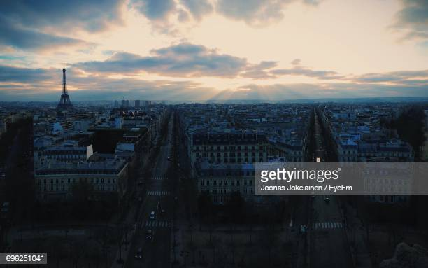 Mid Distance View Of Eiffel Tower Amidst Cityscape Against Sky During Sunset