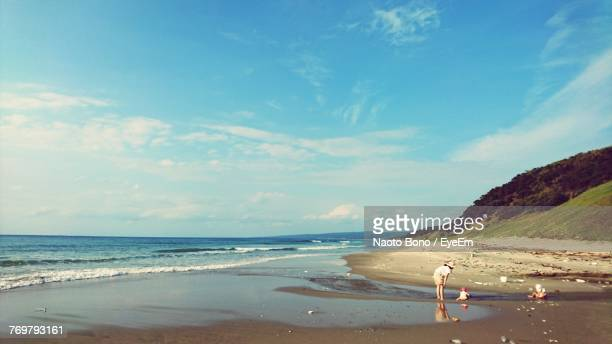Mid Distance View Of Family At Beach Against Blue Sky