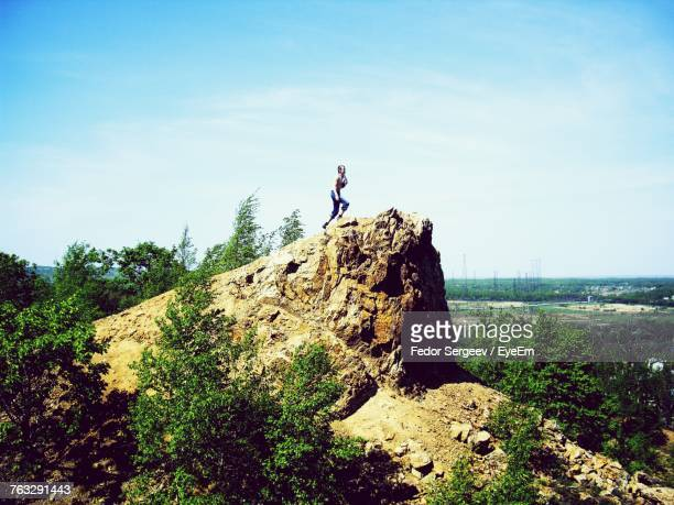mid distance view of female hiker climbing on cliff against sky - fedor stock pictures, royalty-free photos & images