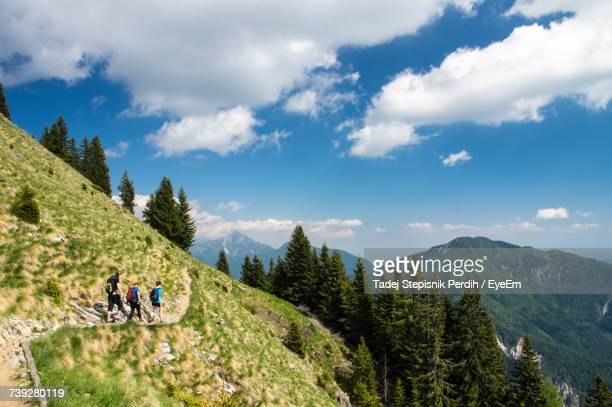 Mid Distance View Of Hikers Hiking On Mountain Against Sky