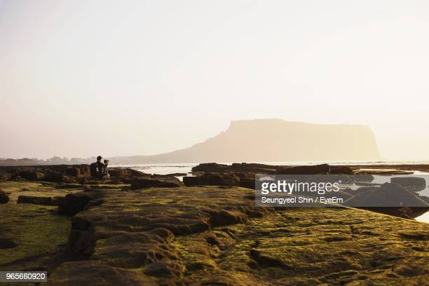 Mid Distance View Of Man Photographing On Rocks At Beach Against Sky