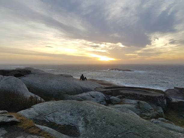 Mid Distance View Of Man Sitting On Rock At Beach Against Cloudy Sky During Sunset