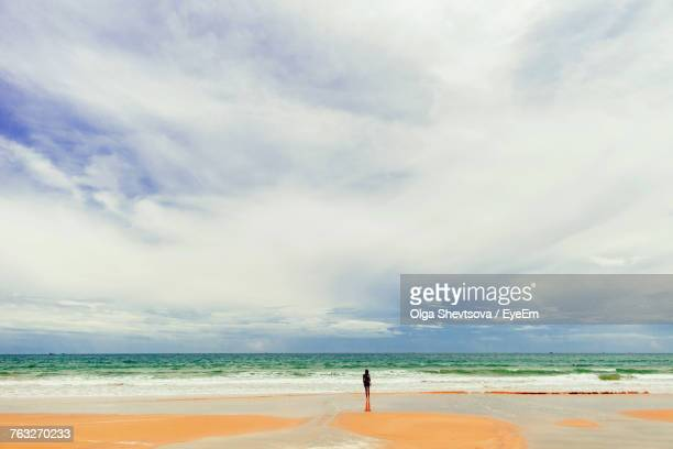 Mid Distance View Of Man Standing At Beach Against Cloudy Sky