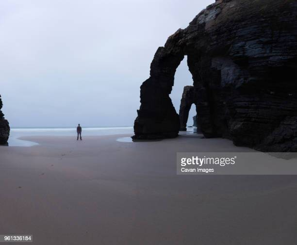 mid distance view of man standing by rock arch at cathedral beach against sky - galizia foto e immagini stock