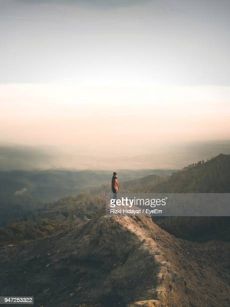 mid distance view of man standing on cliff against sky - mid distance stock pictures, royalty-free photos & images