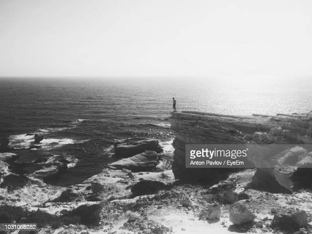 mid distance view of man standing on cliff by sea against sky - rocky coastline stock pictures, royalty-free photos & images