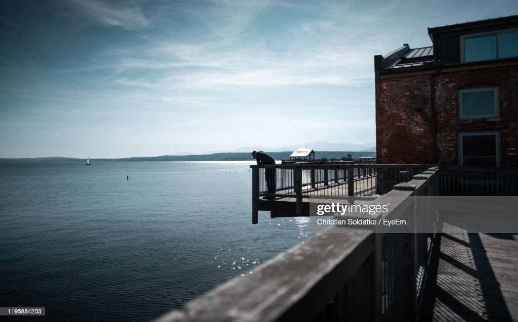 Mid Distance View Of Man Standing On Footbridge Over Sea : Stock-Foto