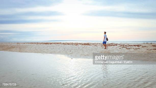 Mid Distance View Of Man Walking On Shore At Beach Against Sky