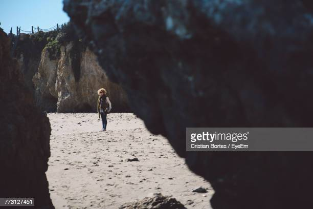 Mid Distance View Of Mid Adult Woman At Beach Seen Through Rocks
