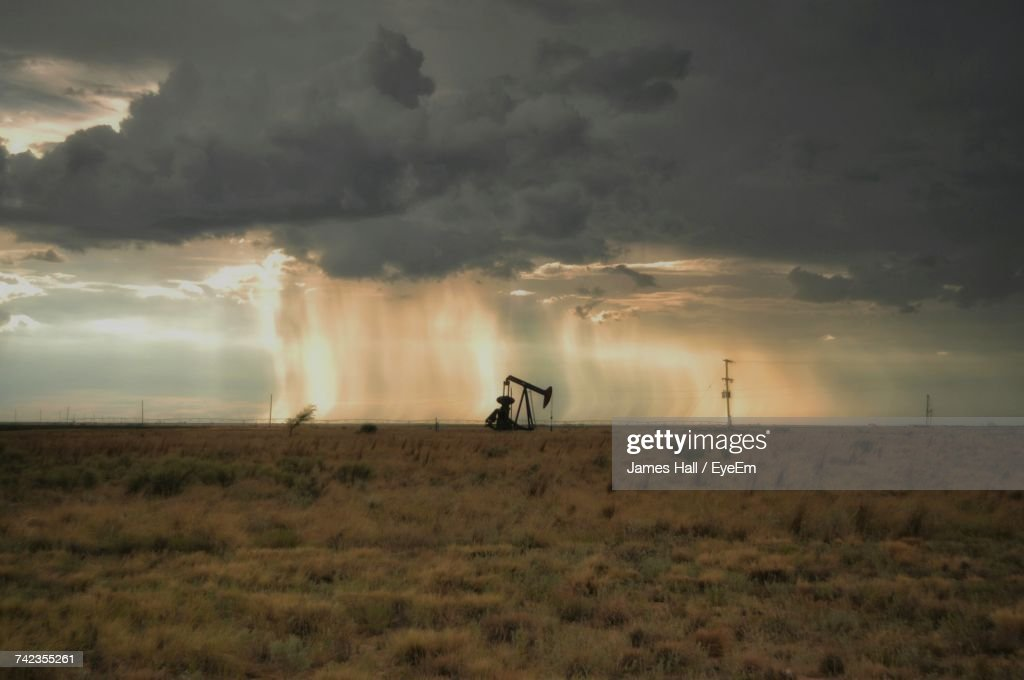 Mid Distance View Of Oil Well On Field Against Cloudy Sky During Sunset : Stock Photo