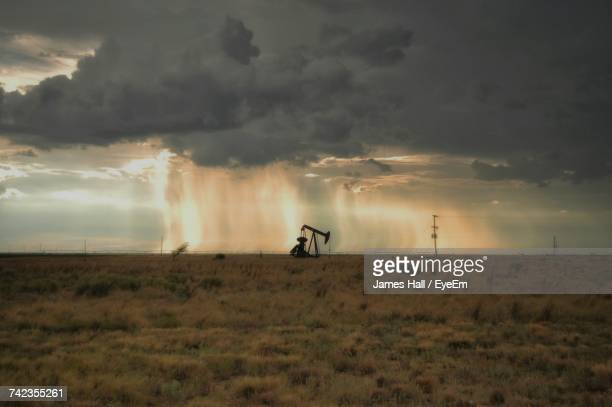 Mid Distance View Of Oil Well On Field Against Cloudy Sky During Sunset