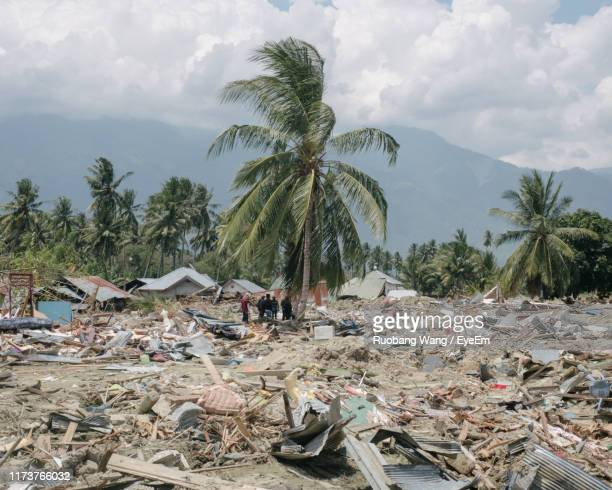 mid distance view of people standing amidst tsunami destruction against cloudy sky - climate stock pictures, royalty-free photos & images