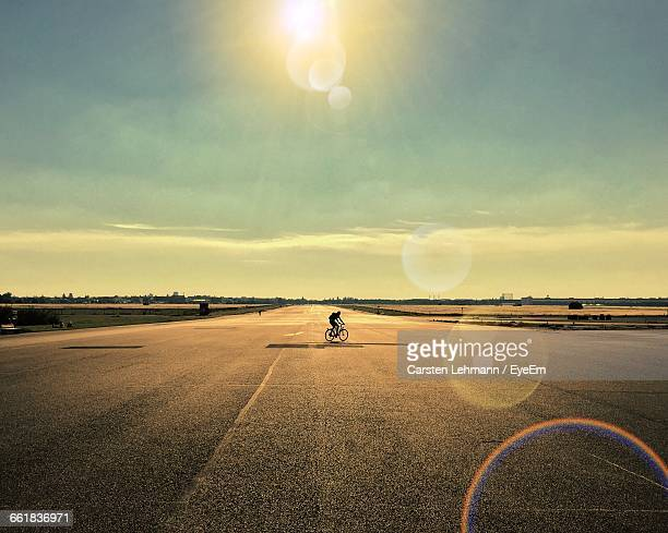 Mid Distance View Of Person Riding Bicycle On Road Against Sky During Sunny Day