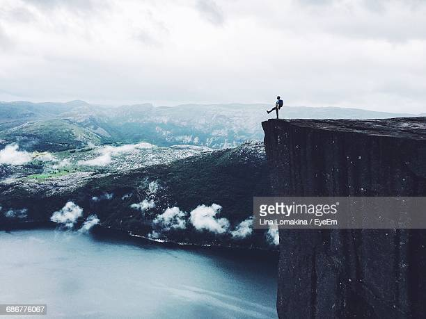 mid distance view of person standing at the edge of cliff by sea - moed stockfoto's en -beelden