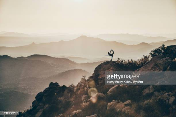 Mid Distance View Of Silhouette Woman Exercising On Rock Against Mountains During Sunset