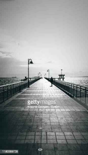 mid distance view of silhouette woman walking on footpath against sky during sunny day - krasimir georgiev stock photos and pictures