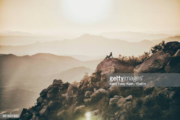 mid distance view of woman sitting on rocks against mountains and clear sky - kerry estey keith stock photos and pictures