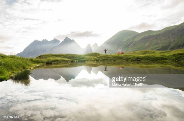 Mid Distance View Of Woman Standing At Lakeshore Against Mountains