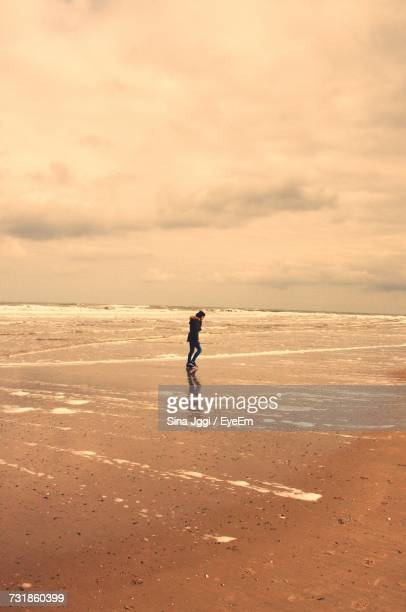 Mid Distance View Of Woman Walking On Shore At Beach Against Sky
