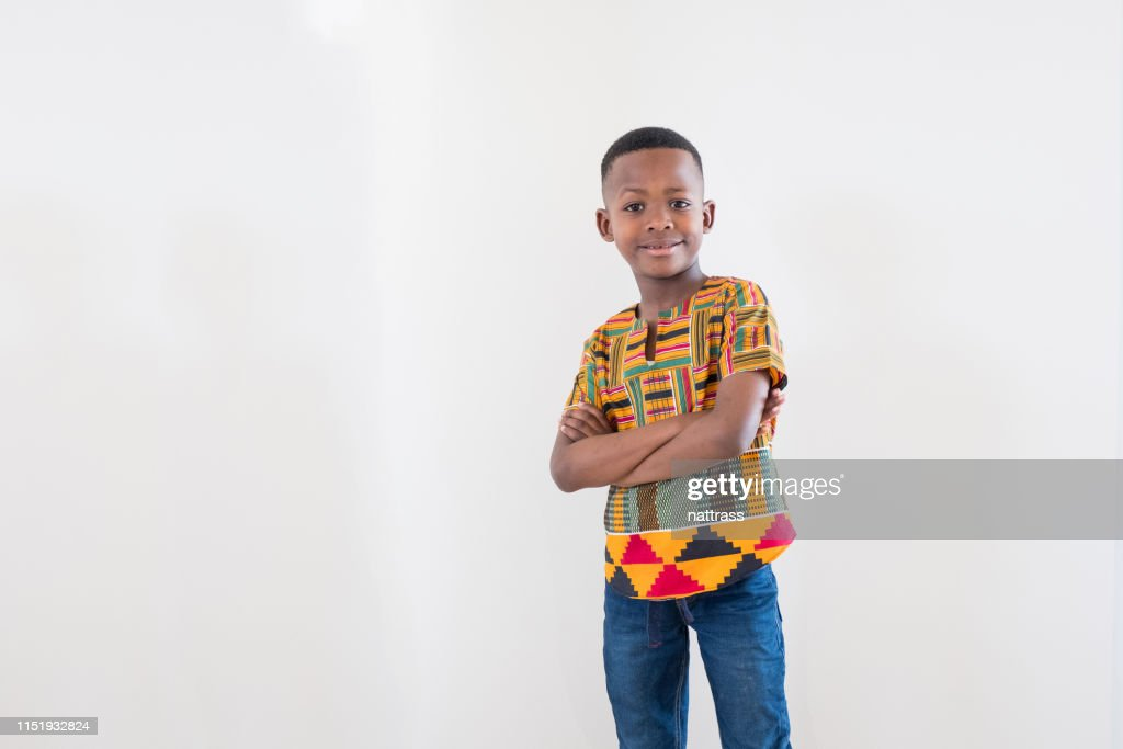 Mid length portrait of smiling boy with arms crossed : Stock Photo