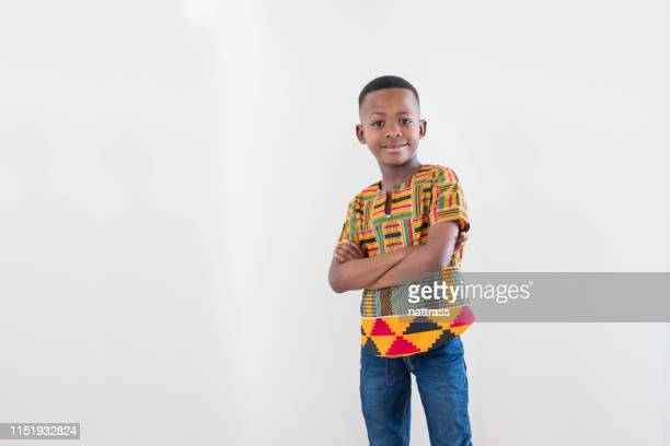 mid length portrait of smiling boy with arms crossed - dashiki stock photos and pictures