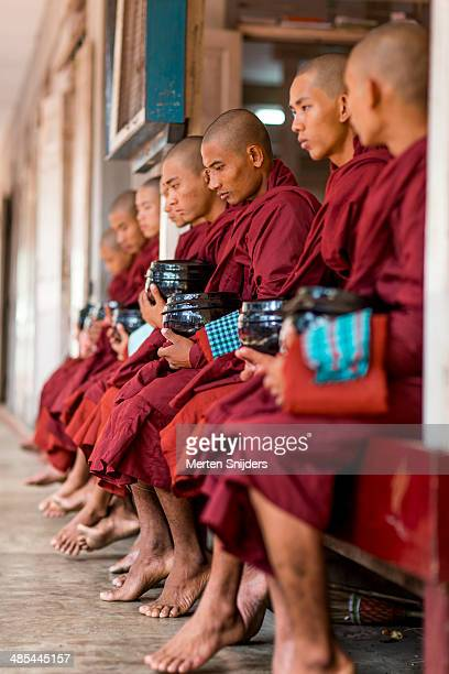 mid level buddhist monks seated with bowl - merten snijders stockfoto's en -beelden