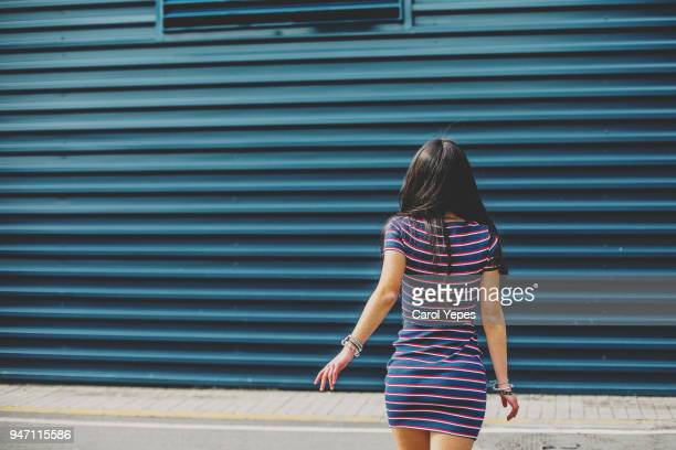 mid section brunette teenager walking away against blue wall - striped dress stock photos and pictures