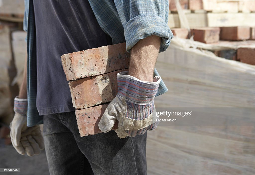 Mid Section of a Bricklayer Carrying Three Bricks With Protective Gloves : Stock Photo